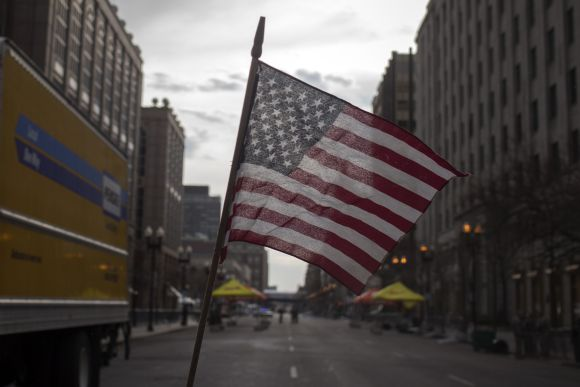 An American flag waves from a make shift memorial on Boylston Street a day after Boston blasts