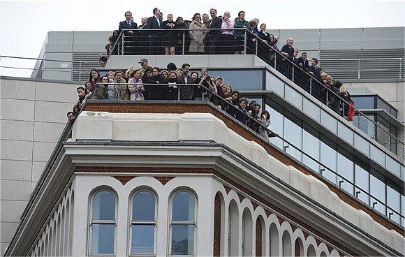 Office workers on balconies watch the funeral procession