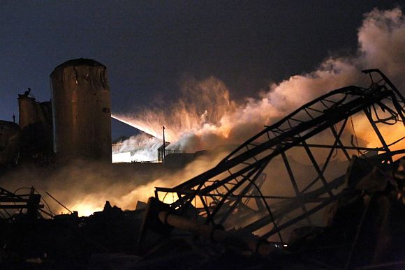 Smoke rises as water is sprayed at the burning remains of a fertilizer plant after an explosion at the plant in the town of West, near Waco, Texas