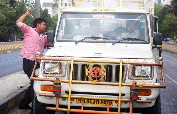 A protestor attacks a vehicle as bandh crippled normalcy in Thane city on Thursday
