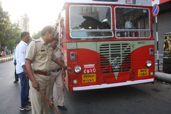 Police inspect a damaged bus as bandh against the ongoing demolition drive paralysed life in Thane on Thursday