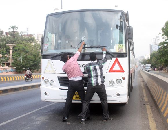 Protestors damage a bus during Thane bandh on Thursday