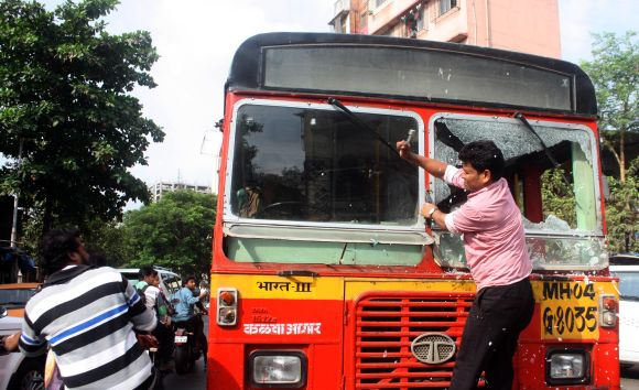 A protestor attacks a government bus as normalcy was crippled during Thursday's Thane bandh