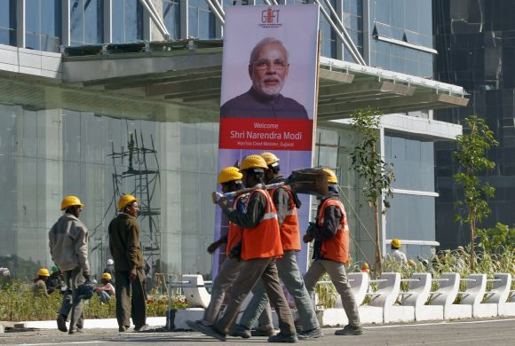 Workers walk past a poster of Gujarat's Chief Minister Narendra Modi installed at the construction site of Gujarat International Finance Tec-City (GIFT) building at Gandhinagar