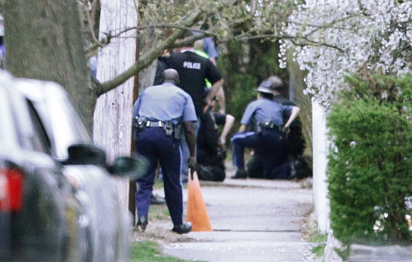 Police officers move towards a police assault on a house with their guns drawn as gunfire erupts on Franklin Street during the search for Dzhokhar Tsarnaev