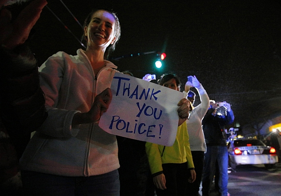 Members of the public cheer as police officers leave the scene where Dzhokhar was taken into custody in Watertown, Massachusetts