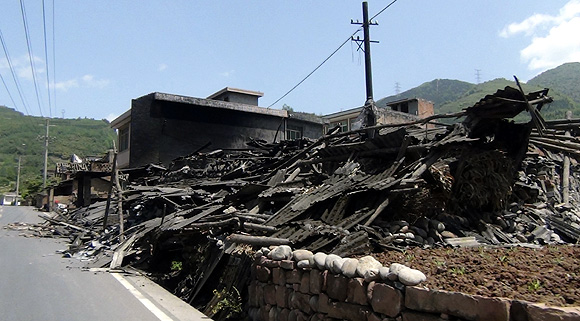 Collapsed houses are seen after an earthquake of 6.6 magnitude, on the side of a road leading from Ya'an city to Luzhou County