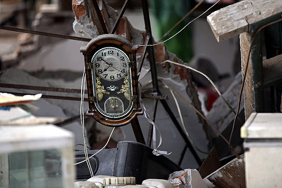 A clock is seen amidst the debris of a collapsed house after a strong 6.6 magnitude earthquake, at Longmen village, Lushan County