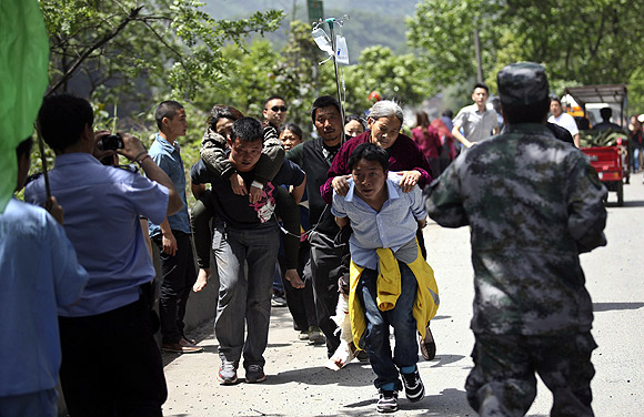 Men carry injured people to an ambulance at Longmen Village, Lushan County