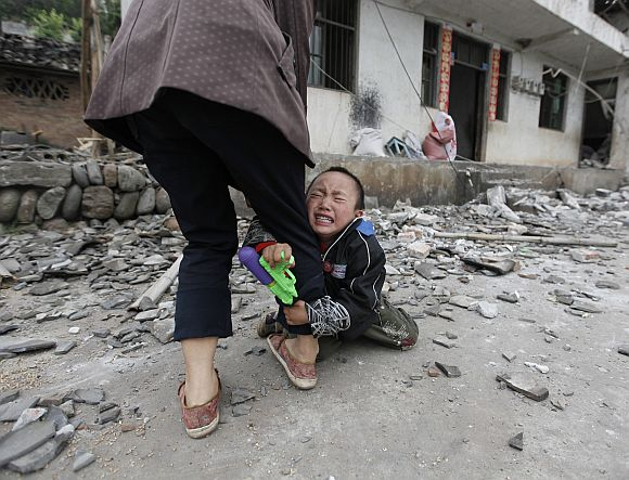 A boy holds his mother's leg as he cries in front of their damaged house