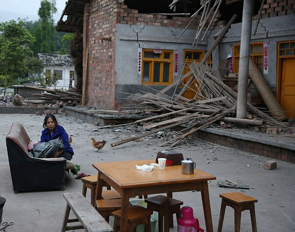 A woman sits outside a heavily damaged building in the Gonghe village