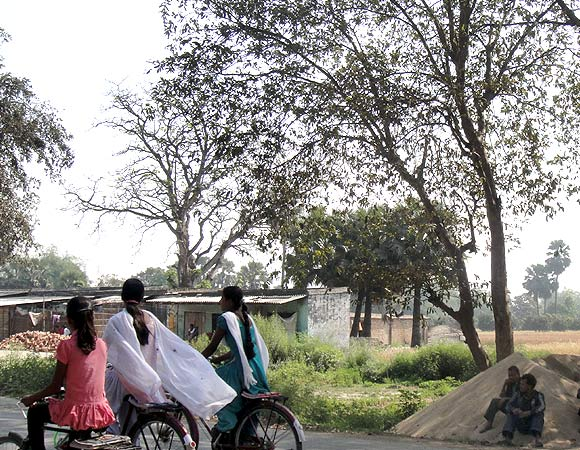 Girls cycle on a road in North Bihar