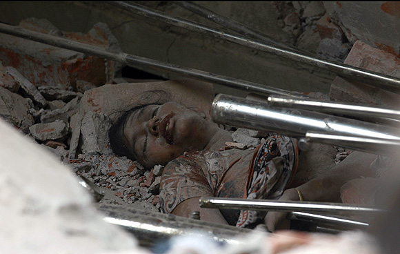 The body of a garment worker is seen amongst the rubble