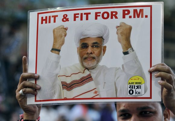 A BJP supporter holds a poster featuring Narendra Modi during a jubilation ceremony outside the party office in Ahmedabad.