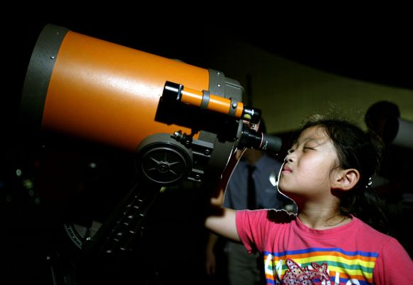 A Chinese girl takes a closer view of Mars through a telescope in Shanghai
