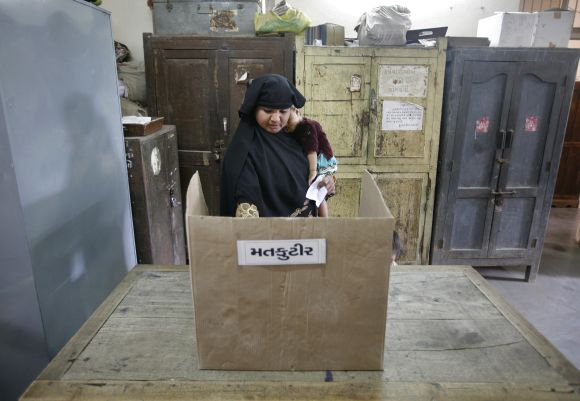 A woman casts her vote at a polling booth in Gujarat