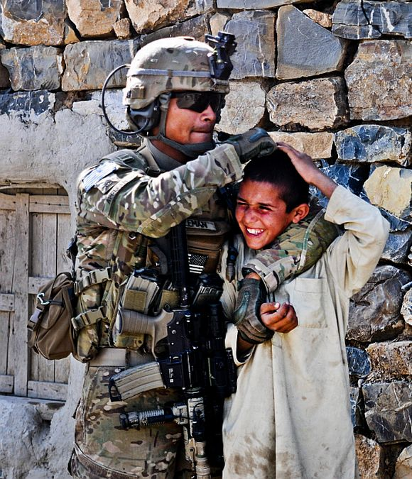 United States Army Staff Sergeant Christian Aleman, from Miami, a squad leader assigned to A Battery, gives a playful nudge to a Afghan boy while out on patrol