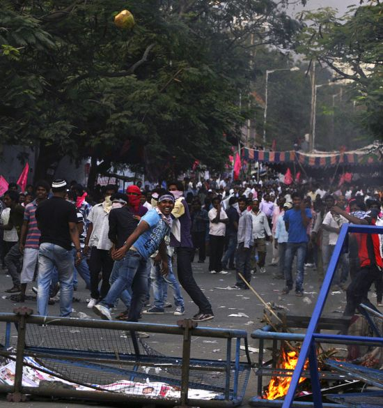 A pro-Telangana supporter throws a coconut towards police during a protest in Hyderabad.