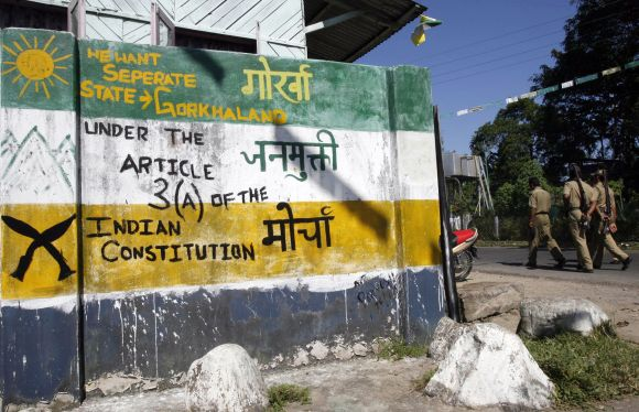 Policemen walk past a graffiti demanding a state of Gorkhaland at Sukuna village in Darjeeling