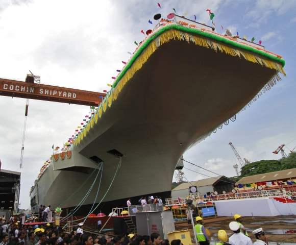 Employees of Cochin shipyard stand beside India's indigenous aircraft carrier P-71 Vikrant built for the Indian Navy during its launch in Kochi
