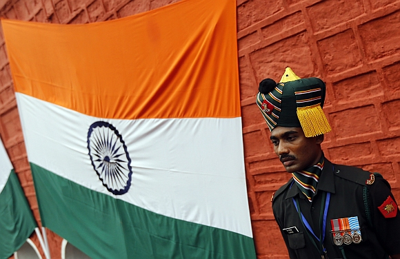 An Indian soldier stands next to an Indian national flag during the full-dress rehearsal for Independence Day celebrations at the historic Red Fort in Delhi.