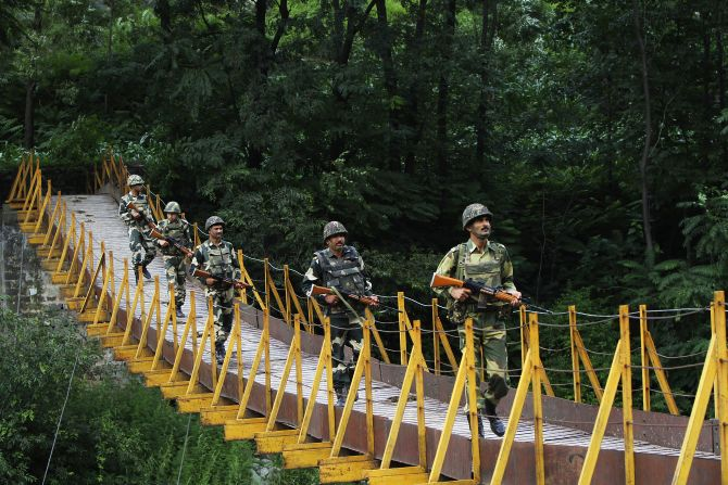 BSF soldiers patrol over a footbridge built over a stream near the Line of Control at Sabjiyan sector of Poonch district.