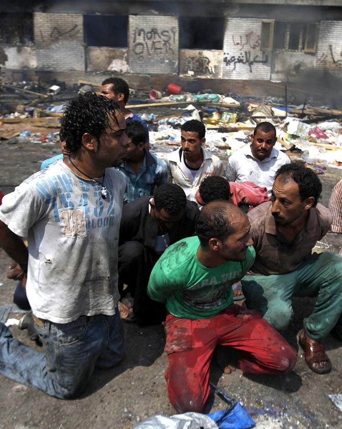 Suspects are rounded up near a burnt annex building of Rabaa Adawiya mosque after the clearing of a protest camp around the mosque, in Cairo