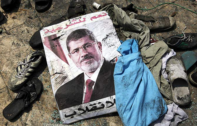 A poster of deposed Egyptian President Mohamed Mursi that reads 'Yes to legitimacy; no to the coup' lies amid the debris of a cleared protest camp