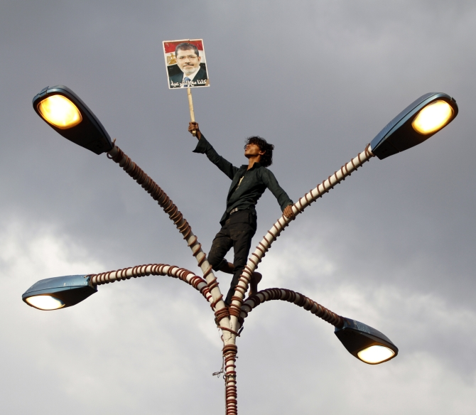 A supporter of deposed Egyptian President Mohamed Morsi holds up his photo while standing at the top of lamp posts during a march to show solidarity with his supporte