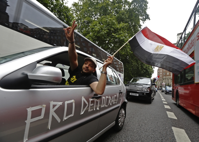 Supporters of Morsi demonstrate as they slow drive through central London