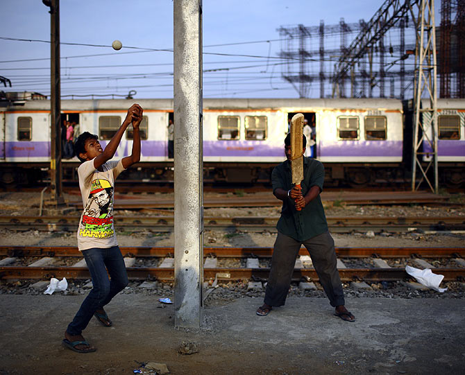 Boys play cricket along the tracks as a local train passes by in Mumbai