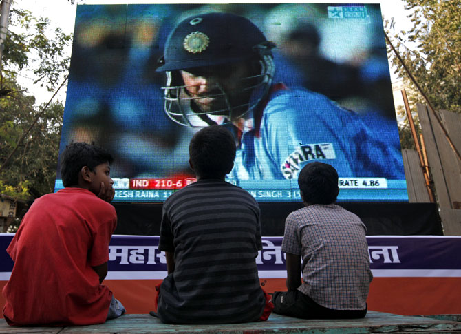 Children watch a cricket match on a big screen in Mumbai