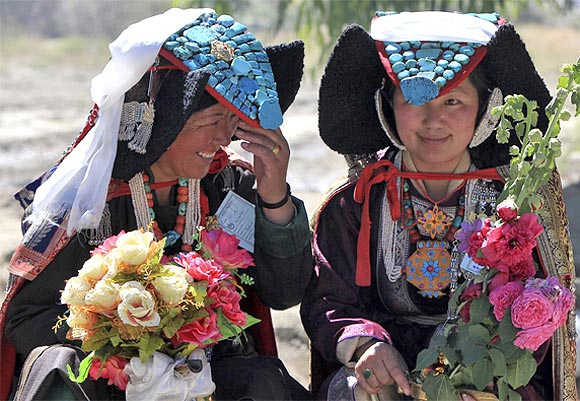 Ladakhi women wait to welcome Tibetan spiritual leader the Dalai Lama in Leh July 29, 2013.