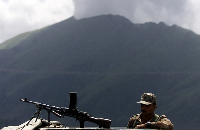 An army soldier keeps watch during a presentation of killed terrorists to media by the Indian army at an altitude of 11,000 feet at Keran sector, some 180 km from Srinagar