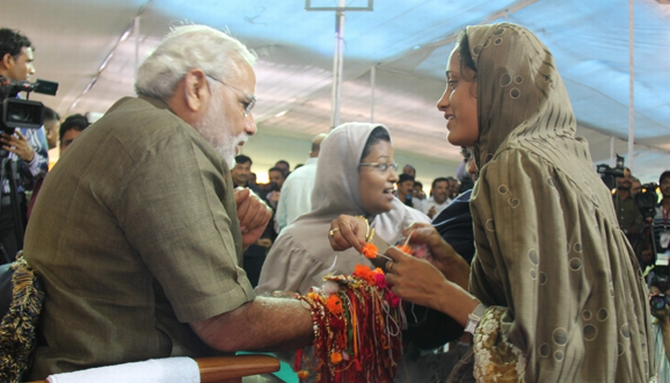A Muslim woman ties a 'rakhi' to Narendra Modi on Tuesday