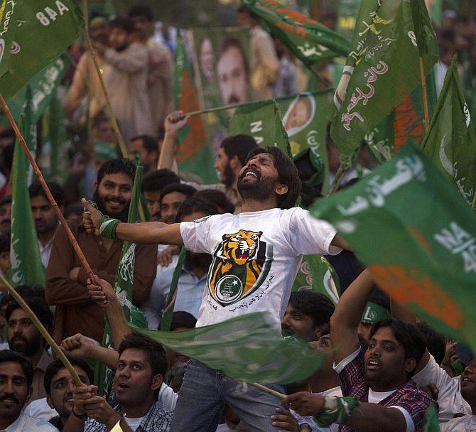 A supporter of the Pakistan Muslim League -- Nawaz (PML-N) party shouts slogans with others waving the party flags
