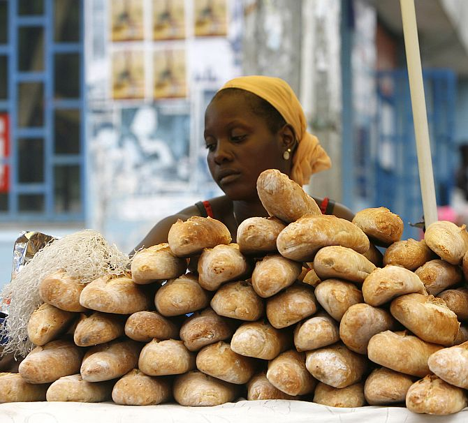 A bread seller waits for customers at Nafaya Junction in Conakry