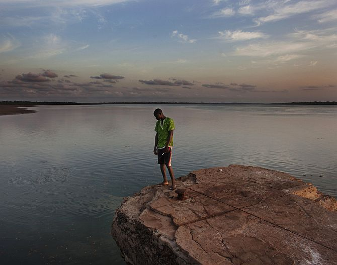 student Rachid Malam peers off the edge of a colonial-era dock on the island of Bolama in Guinea-Bissau