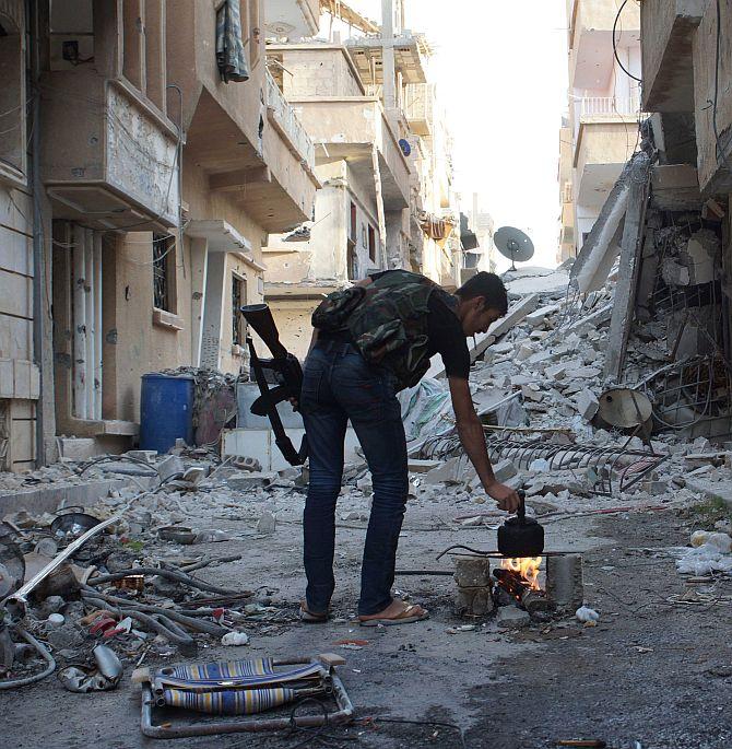A Free Syrian Army fighter makes tea in Deir al-Zor