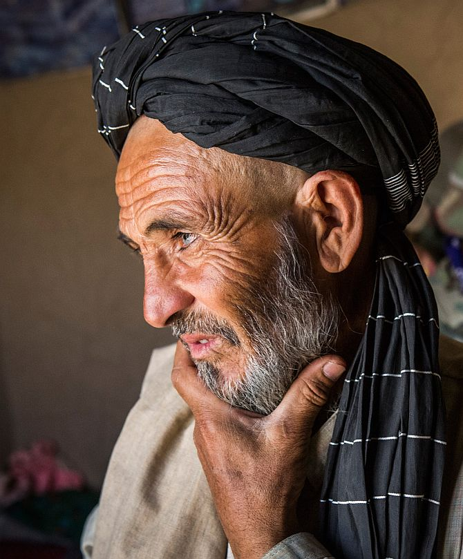 A local Afghan man waits while soldiers in the Afghan National Army's 6th Kandak (battalion), 3rd company search his home