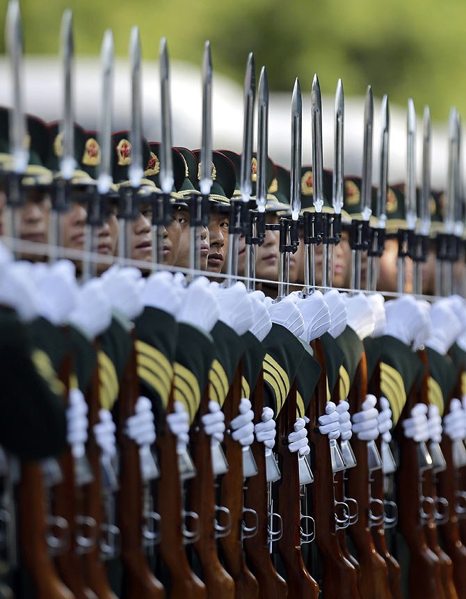 A string is used to to ensure an honour guard stands in a straight line ahead of a welcoming ceremony outside the Great Hall of the People in Beijing.