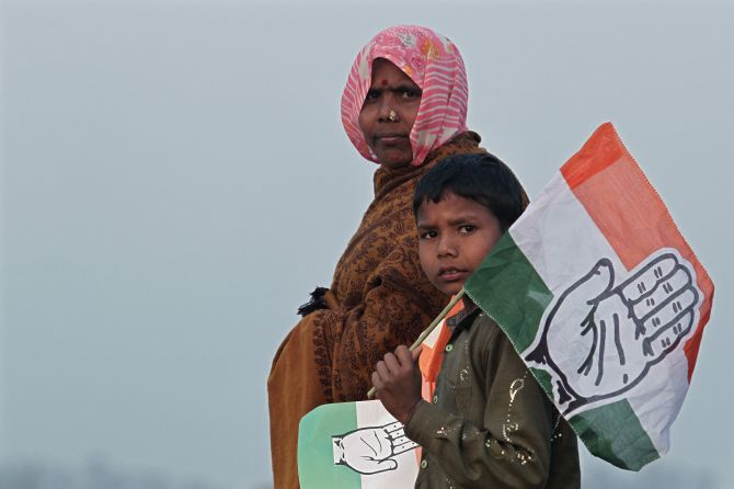 Supporters holding flags of India's ruling Congress party leave after attending an election campaign rally by Rahul Gandhi in Uttar Pradesh