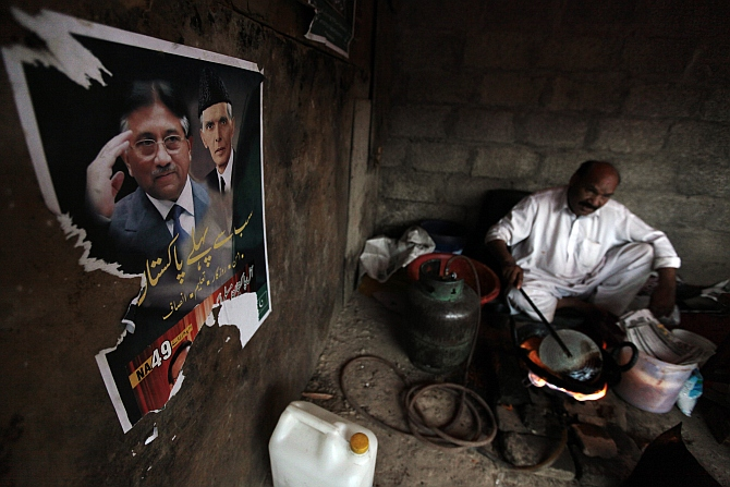 A poster of former Pervez Musharraf, with Muhammad Ali Jinnah, founder and first governor-general of Pakistan, is pictured on a wall as a man prepares snacks in Islamabad