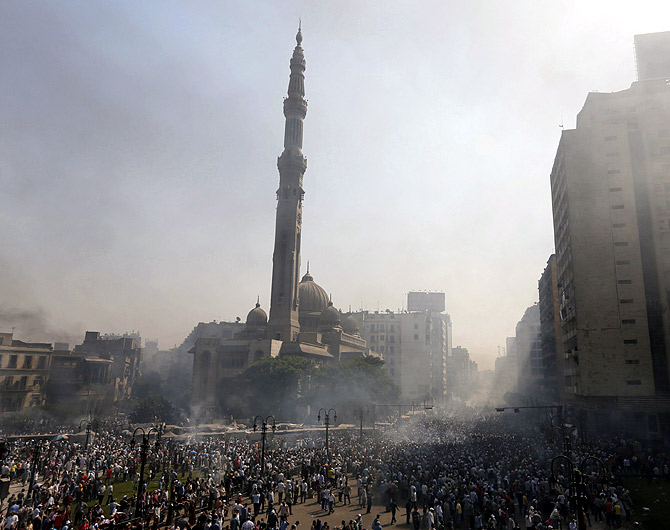 Members of the Muslim Brotherhood and supporters of ousted Egyptian President Mohamed Mursi flee from shooting in front of Azbkya police station during clashes at Ramses Square in Cairo