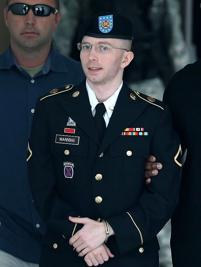 US Army Private First Class Bradley Manning is escorted by military police as he leaves his military trial