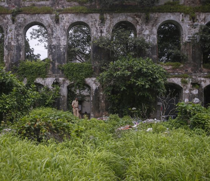 Policemen stand guard near the crime scene where a photo journalist was gang-raped inside an abandoned textile mill in