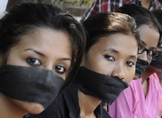 Members of the All Assam Photojournalist Association wear black sashes around their mouths during a protest against the rape of a photojournalist by five men in Mumbai
