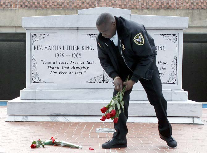 King Centre security officer Kevin Baxter collects roses left at the crypt of Dr Martin Luther King, Jr in Atlanta.