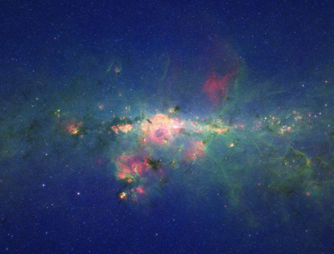 The region around the centre of our Milky Way galaxy glows colorfully in this image taken by Spitzer telescope.