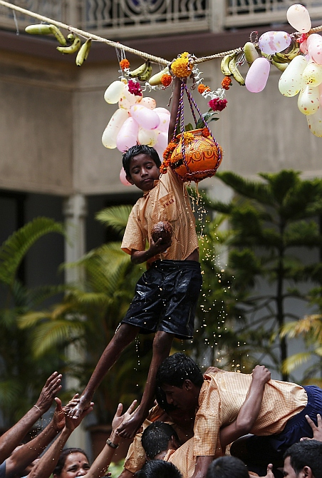 A visually impaired student breaks a clay pot containing curd during celebrations for the Janmashtami in Mumbai.